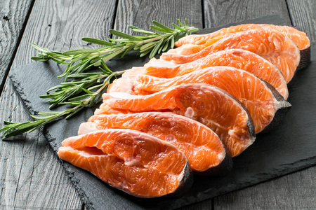 Fresh salmon sliced on steaks on slate plate with rosemary. Preparation for cooking fish. Salmon is source of protein, Omega-Z and vitamin D. Important product in diet and healthy nutrition Stock Photo