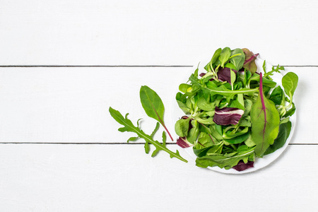 Different salad leaves on a plate on white wooden. Fresh mix of green leaves, ingredients for salad. Concept of diet and healthy food. Top view