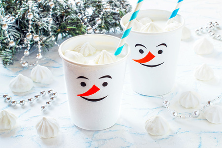 Banana milkshake with snowballs of meringue in glasses in form of funny snowmen. Homemade applique on glasses. Idea for childrens Christmas party. DIY concept of merry Christmas and happy new year