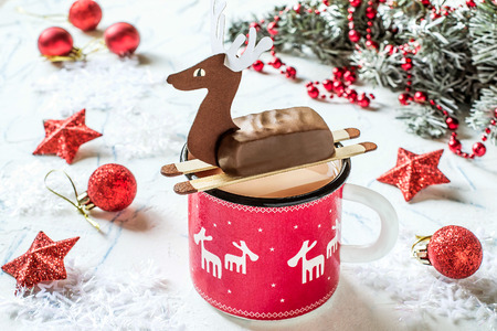 Hot chocolate with chocolate bars in form of Christmas deer. Idea of homemade design for childrens Christmas party. DIY concept of merry Christmas and happy new year. Selective focus