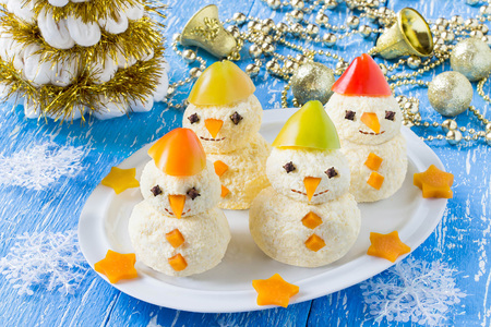 Idea for Christmas party: funny snowmen from cheese and sweet pepper on plate. Original snack with Christmas and New Year. Blue wooden background with christmas decorations Lizenzfreie Bilder