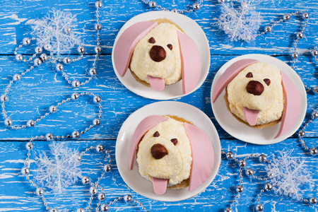 Idea for festive party: funny dogs from cheese, sausages and nuts. Original snack for New Year. 2018 is year of dog according to eastern calendar. Blue wood background with celebratory decorations