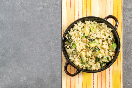 Bowl with couscous, avocado, mint and nuts on gray background with yellow napkin. Salad is seasoned with lemon juice, honey and olive oil. Dietary and healthy food. Top view