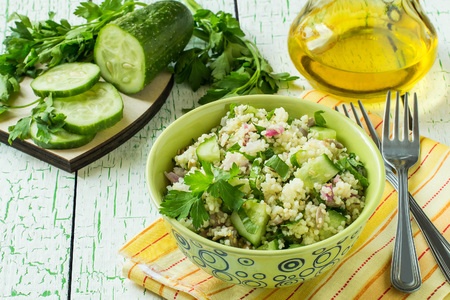 Bowl with couscous, cucumber, parsley, sunflower seeds and sesame on pale green background with yellow napkin. Vegetable ingredients on table and olive oil. Dietary and healthy food