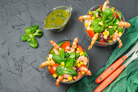 Fresh salad with shrimps, tomatoes, sweet pepper, corn and green salad leaves. Served with vinaigrette sauce. Concept of diet and healthy food. Glass bowls with salad, green gauze napkin and forks Lizenzfreie Bilder