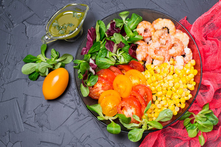 Healthy lunch bowl with tomatoes, corn, various salad leaves and shrimps on gray background with red gauze napkin. Balanced food. Concept of dietary and healthy eating. Top view