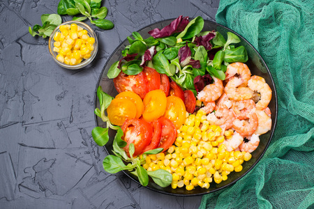 Healthy lunch bowl with tomatoes, corn, various salad leaves and shrimps on gray background with green gauze napkin. Balanced food. Concept of dietary and healthy eating. Top view Lizenzfreie Bilder