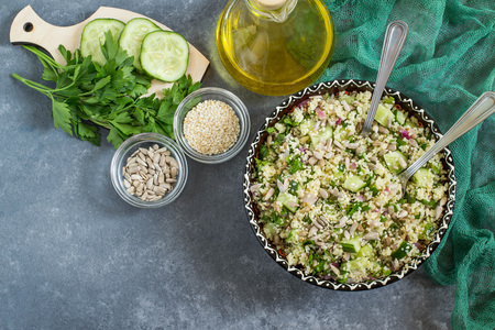 Bowl with couscous, cucumber, parsley, sunflower seeds and sesame on gray background with green napkin. Dietary and healthy food. Top view Lizenzfreie Bilder