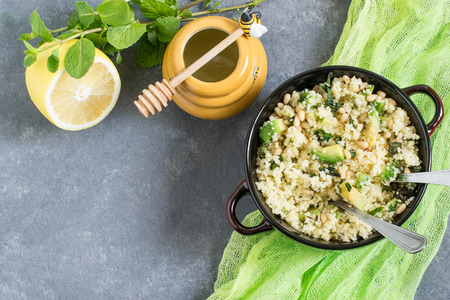 Bowl with couscous, avocado, mint and nuts on gray background with green napkin. Salad is seasoned with lemon juice, honey and olive oil. Dietary and healthy food. Top view