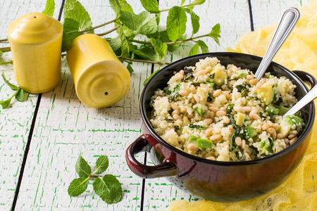 Bowl with couscous, avocado, mint and nuts on pale green background with yellow napkin. Salad is seasoned with lemon juice, honey and olive oil. Dietary and healthy food