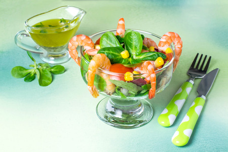 Fresh salad with shrimps, tomatoes, sweet pepper, corn and green salad leaves. Served with vinaigrette sauce. Concept of diet and healthy food. Festive serving in glass dessert bowl