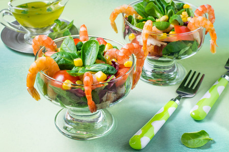 Fresh salad with shrimps, tomatoes, sweet pepper, corn and green salad leaves. Served with vinaigrette sauce. Concept of diet and healthy food. Festive serving in glass dessert bowls