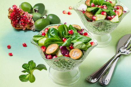 Fresh salad with cucumbers, feijoa, pomegranate seeds and green lettuce leaves. Served with vinaigrette sauce. The concept of diet and healthy food. Festive serving in glass dessert bowls