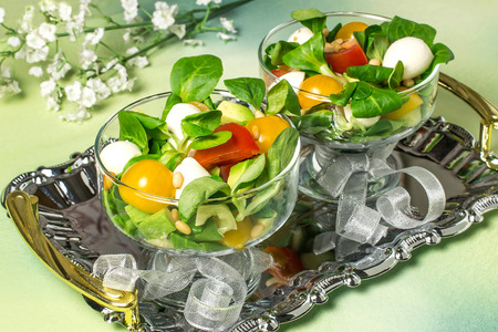Fresh salad with mozzarella, tomatoes, sweet pepper, avocado and salad leaves. Concept of diet and healthy food. Two dessert bowls with salad on metal shiny tray, festive serve Lizenzfreie Bilder