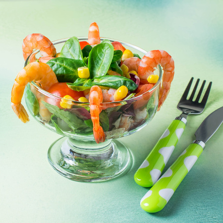 Fresh salad with shrimps, tomatoes, sweet pepper, corn and green salad leaves. Served with vinaigrette sauce. Concept of diet and healthy food. Festive serving in glass dessert bowl. Square image