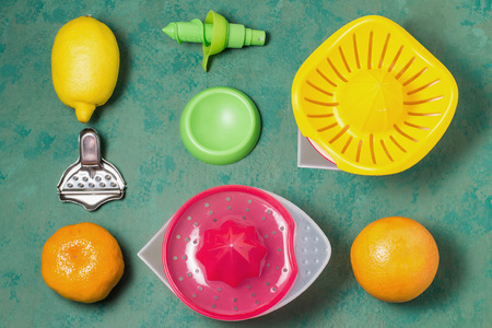 Various devices for squeezing juice from citrus: hand juicer, press for slices of lemon, pump for spray. Fresh fruit lemon, orange, mandarin for making juice. Green background, top view, flat lay