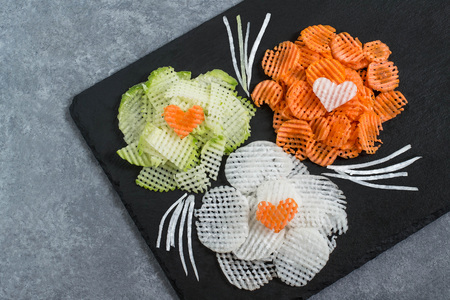 Figured slicing vegetables for vitamin salad. Flowers from carrot, daikon and radishes on slate plate. Detox product. Vegetarian, healthy and diet food. Culinary improvisation on Valentines Day theme
