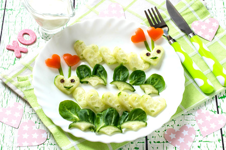 Design of breakfast for Valentines Day. Fun loving caterpillars, carved in shape of hearts of cucumber. Healthy and vegetarian food. Symbols of Valentines Day in design