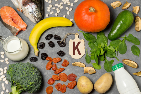 Food is source of potassium. Various natural food rich in vitamins and micronutrients. Useful food for health and balanced diet. Prevention of avitaminosis. Small cutting board with name of potassium Stock Photo