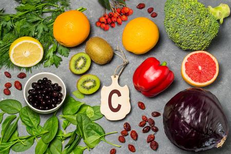 A comida é fonte de vitamina C. Vários alimentos naturais ricos em vitaminas. Alimentos úteis para a saúde e dieta equilibrada. Prevenção de avitaminose. Tábua de cortar pequena com nome da vitamina C. Vista superior