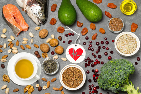 Food products useful for heart. Set of natural food products are sources of vitamins and minerals. Tag with homemade application from paper - symbol of heart. Top view