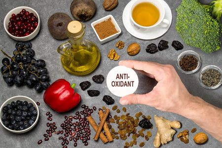Food sources natural antioxidants. Antioxidants neutralize free radicals, have beneficial health effects. Group includes minerals, carotenoids and vitamins. Mans hand holds tag with word antioxidant