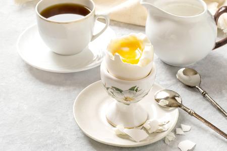 Uovo alla coque in portauovo in ceramica, caffè e panna. Uovo rotto fresco bollito con tuorlo d'arancia liquido, pezzi di guscio e cucchiaio sul piatto. Concetto di colazione. Messa a fuoco selettiva Archivio Fotografico - 94109771