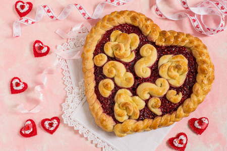 Delicious festive cake for Valentines Day in form of heart. Prepared from yeast dough with raspberry jam. Original baking, creative design Stock Photo