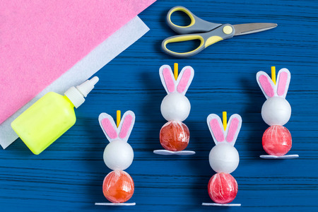 Making Easter bunny from lollipop. Sweet gift to children. Creative idea for childrens party. DIY concept. Step by step photo instructions. Step 6. Stick paws and ears to lollipop