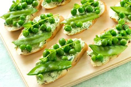 Fresh spring toast with cottage cheese and herbs, green peas and sprouts of mint. Idea of recipe. Cottage cheese is mixed with parsley, garlic and dill. Green peas blanched. Dietary and healthy food