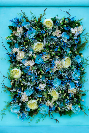 Colorful flower arrangement of blue roses, greenish-white ranunculus, other flowers, leaves and roots on blue wooden background. Festive design of premises. Painting from flowers
