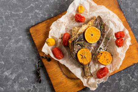 flet cuit aux mandarines et aux fruits de cerises . poisson avec des légumes et des fruits sur le papier cuisson et vieille planche à découper