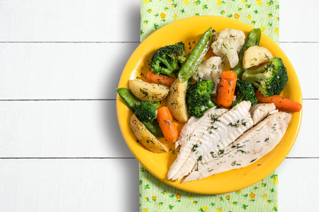 Flounder baked with vegetables. Plate with fish, broccoli, carrots, potatoes and peas. Dietary and healthy food
