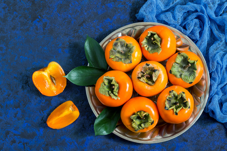 Ripe persimmon on metal plate with blue gauze napkin on blue textured background. Persimmon is source of vitamin C, iodine, iron, potassium and magnesium. Useful for prevention of cardiovascular disease
