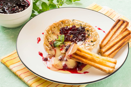 Brie cheese baked with bread crumbs and thyme. Served with cranberry sauce and grilled bread sticks. Molten cheese flows onto plate, grilled breadstick in cheese with sauce