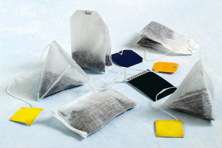 Several tea bags of different shapes and with different kinds of tea on light blue background. Tea bags are used for fast brewing tea