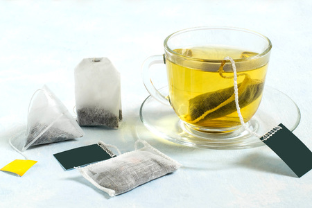 Several tea bags of different shapes and with different kinds of tea and cup of tea on light blue background. Tea bags are used for fast brewing tea Stock Photo