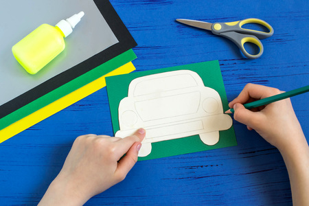 Making greeting card for Father's Day in shape of car. Children's art project. DIY concept. Step-by-step photo instruction. Step 2. Child draws car using template