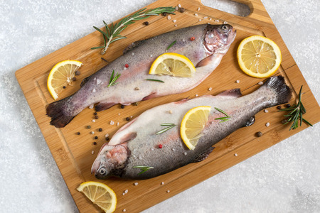 Two fresh trout on cutting board and ingredients for cooking (pepper, salt, lemon, seasoning and rosemary). Dietary and healthy food