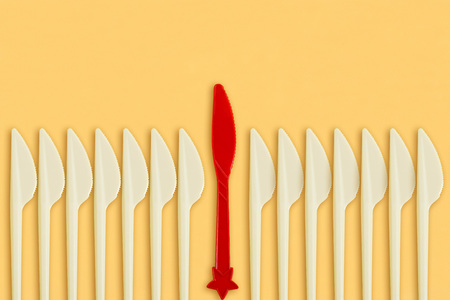 Red plastic knife among white on yellow background. Minimal style. Creative idea, imagination and fantasy. Concept of leadership, individuality, difference from others Stock Photo