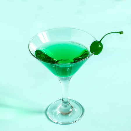 Green cocktail with maraschino cherry in martini glass on pastel blue background. Minimal style. Concept of bright original drinks