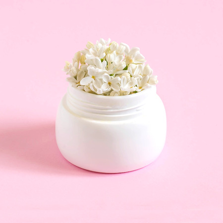 Jar with flowers of white lilac as cosmetic cream on pastel pink background. Minimal style. Creative idea, imagination and fantasy. Concept of natural cosmetics Stock Photo