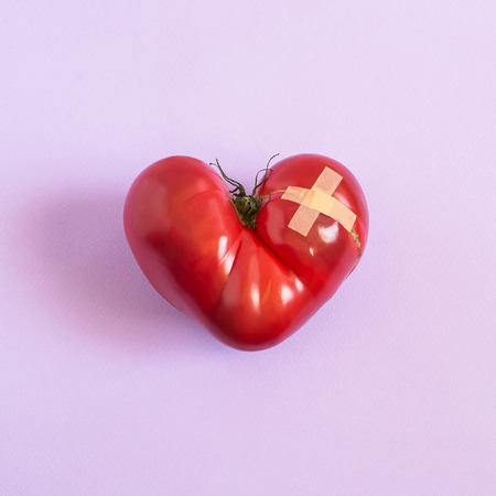 Big tomato in shape of wounded heart with adhesive plaster on lilac pastel background. Minimal style. Jokes of nature, imagination and fantasy. Foods useful for heart Stock Photo