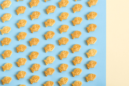 Cookies in form of small fish on blue background. Many small fish are arranged in rows. Food background