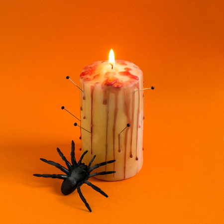 Homemade decor for Halloween. Candle pierced with needles with red brooks and drops like blood and spider on orange background. Minimal style. Original design