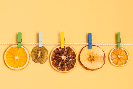 Slices of fruit (orange, kiwi, grapefruit, apple, lemon) dried on rope with clothespins. Creative idea, imagination and fantasy. Minimal style, yellow background with copy space. Food artistic concept Archivio Fotografico