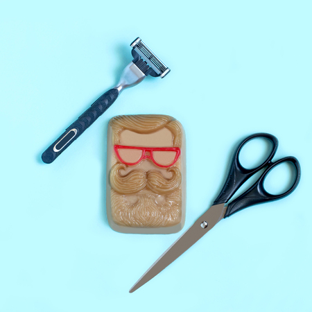 Handmade soap in form of face with mustache, scissors and razor. During November men grow mustache to draw attention to problem of mens health, carry out fundraising action. Minimal concept Reklamní fotografie