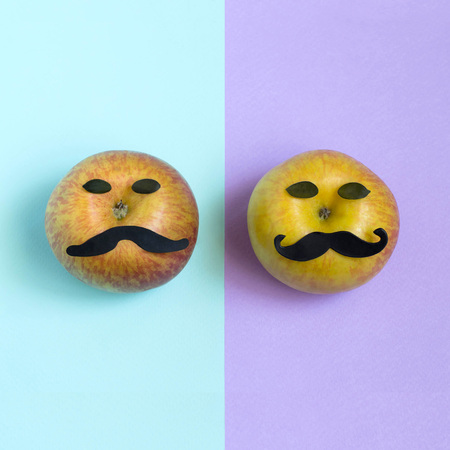 Two apples with mustache on two-color background. Creative idea for mustache season, month of raising awareness about prostate cancer and drawing attention to issue of mens health. Minimal style