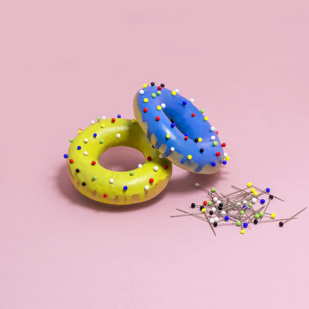 Humorous imitation of donuts from painted bagels with multi-colored pins. Artificial object that mimics natural forms. Joke on theme of food. Minimal style. Creative idea and fantasy. Modern pop art