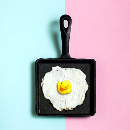 Square cast-iron frying pan with fried eggs, toy duckling instead of yolk. Artificial objects that mimic natural forms. Creative idea, imagination and fantasy. Original minimal concept